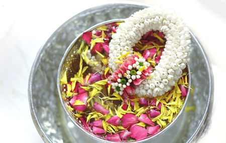 Thai traditional jasmine garland and water in silver bowl