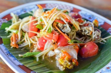 Papaya seafood salad on banana leaf photo