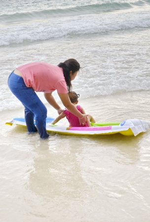 interrogatively: mother take care her child on the beach