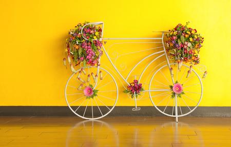 decorated bike: biciclette e fiore decorato a muro giallo.