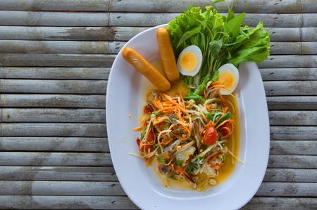 Blue crab papaya salad on bamboo table.