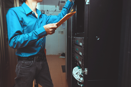 receiver: young engeneer business man with thin modern aluminium laptop in network server room