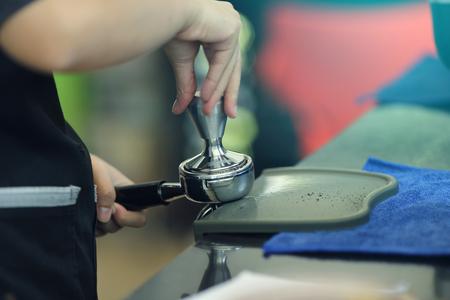 barista woman making coffee by espresso machine at cafe bar or restaurant kitchen