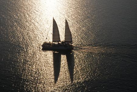 Yacht sailing against sunset Stock Photo