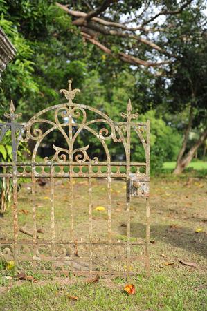 barrier gate: Classical design black wrought iron gate in a beautiful green garden