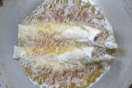 frying fresh fish in a pan photo