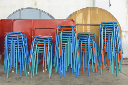cramped space: A lot of chairs arranged in a pile