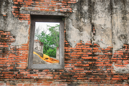 ayuttaya: Ruin and ancient orange brick wall with a window view to the trees of Ayuttaya province in Thailand.