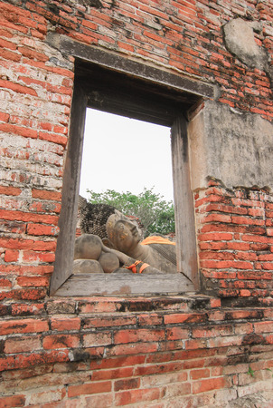 Ruin and ancient orange brick wall with a window view to the trees of Ayuttaya province in Thailand.
