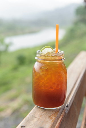 icecube: ice tea with lemon and melissa in mason jars with mountain background.
