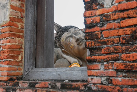 ayothaya: Ruin and ancient orange brick wall with a window view to the trees of Ayuttaya province in Thailand.