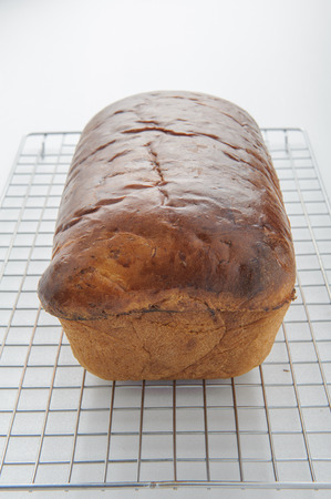 unsliced: Homemade white bread on a wire cooling rack.
