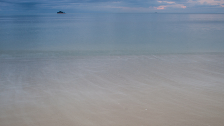 murky: Beautiful clear blue sea ocean water waves hit seashore wet beige sand with splashes spindrifts spoondrifts in rosy murky evening over seascape background