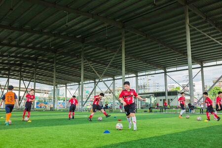 ANGKOK, THAILAND - MAY 6, 2018 :Childrens enjoy playing soccer with coach on holiday at TC football club Rama3.