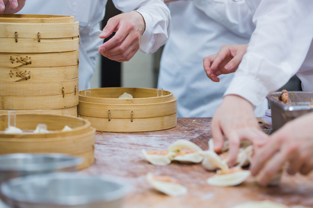 Manufacture of dim sum by Chinese chefs in restaurant.