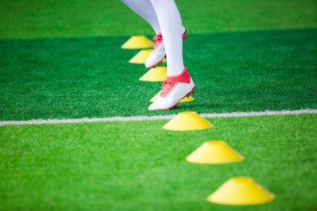 Kid soccer Jogging between marker cones for soccer training of academy. 写真素材