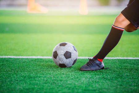 The soccer player shoot ball on artificial turf.