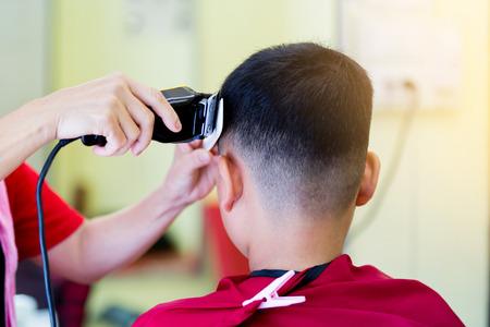Friseurladen. Friseur macht Frisur zu einem asiatischen Jungen mit Haarschneider und weißem Kamm. Modischer Haarschnitt für Jungen.