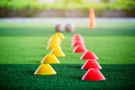 Cone marker and football are soccer training equipment on green artificial turf. Soccer Academy. Stockfoto