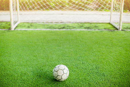 Football on artificial turf and in front of goal. It is for green background and the concept of situation