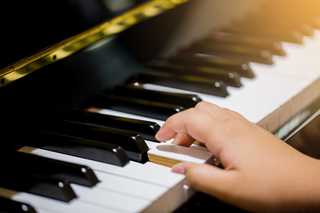 Boy play the piano with selective focus to piano key and hands. There are musical instrument for learning music.