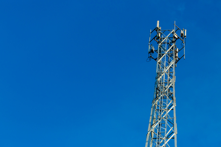 Mobile receiver and transmitter antenna tower,antenna tower building with the blue sky. Stock Photo