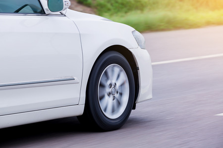 Blurry of white car wheel rotating with running at high speed on road.
