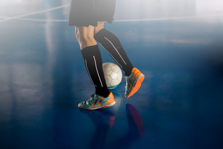 Futsal player  trap and control the ball for shoot to goal. Soccer players fighting each other by kicking the ball. Indoor soccer sports hall. Football futsal player, ball, futsal floor. Sports background. Youth futsal league. Indoor football players with classic soccer ball. Stock Photo