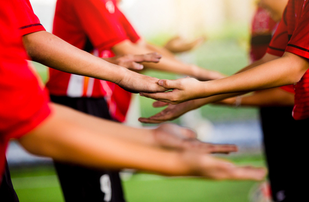 Young boy soccer players tap hands together for football training. Soccer players and goalkeeper traing speed hand together.