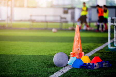 Football and soccer training equipment on green artificial turf with blurry player training background. Soccer Academy.