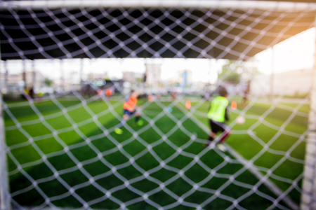Mesh of goal with blurry football player. Soccer ball academy.