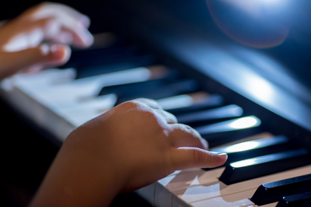Selective focus of kid fingers and  piano key to play the piano with lighting. There are musical instrument for concert or learning music. Stockfoto - 121052593
