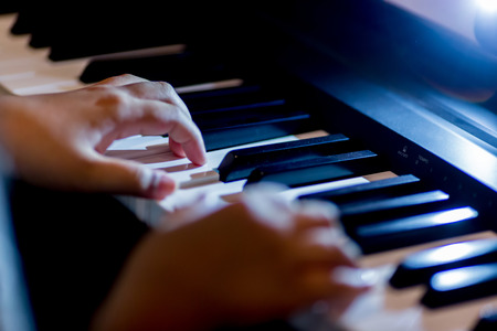 Selective focus of kid fingers and  piano key to play the piano with lighting. There are musical instrument for concert or learning music. Фото со стока