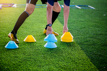 Coach is putting the marker cones for soccer trainng to run and jump. Football academy.