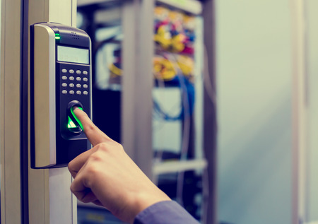 Staff push down electronic control machine with finger scan to access the door of control room or data center. The concept of data security or data access control. Stock Photo