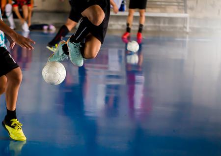 Futsal-Spieler springen mit einer Falle und kontrollieren den Ball, um zum Tor zu schießen. Fußballspieler kämpfen gegeneinander, indem sie den Ball treten. Indoor-Fußballsporthalle. Fußball-Futsal-Spieler, Ball, Futsal-Boden. Standard-Bild