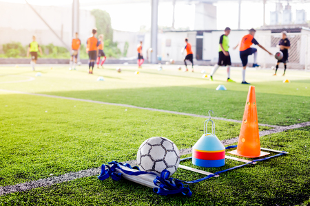 Football and soccer training equipment on green artificial turf with blurry players training background. Soccer Academy.