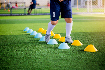 Young boy soccer players Jogging and jump between ladder drills for football training. Ladder drills exercises for football or soccer team. Kid soccer player exercises on ladder drills.