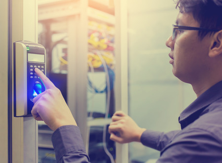 Asian young man press the button of electronic control machine with finger scan to access the door of control room or data center. The concept of data security or data access control.