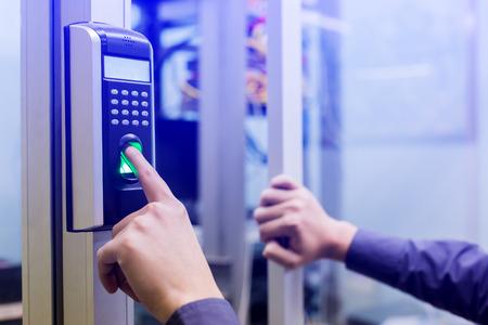 Mitarbeiter drücken elektronische Kontrollmaschine mit Fingerscan herunter, um Zugang zur Tür des Kontrollraums oder des Rechenzentrums zu erhalten. Das Konzept der Datensicherheit oder Datenzugriffskontrolle. Standard-Bild