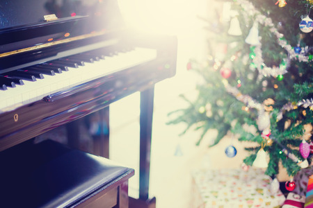 Piano and shine to Christmas tree for christmas holiday background. New Year holidays background.