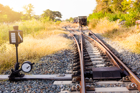 Railroad switch with train in the morning sun. The conception of  change or choices or decide. Trees and grass, yellow sunlight. Railway junction. Heavy industry. Railways.Thailand.