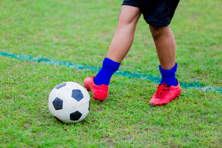 Boy soccer player speed run to shoot ball to goal on green grass. Soccer player training or football match. 스톡 콘텐츠