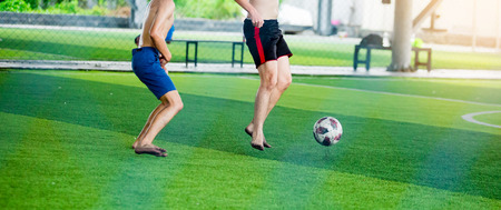Soccer players not wearing a sport shirt and barefoot do trap and control the ball for shoot to goal. Soccer players fighting each other by kicking the ball.