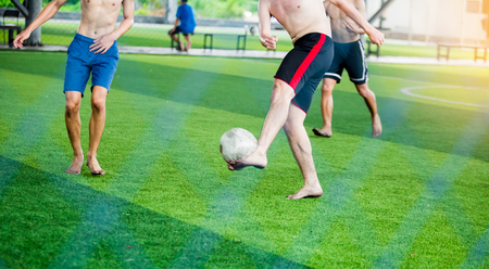 blurry ball after soccer players not wearing a sport shirt and barefoot do trap and control the ball for shoot to goal. Soccer players fighting each other by kicking the ball. 写真素材