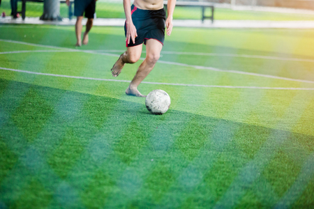 Soccer players not wearing a sport shirt and barefoot do speed run to shoot ball to goal on green artificial turf. Soccer players fighting each other by kicking the ball.