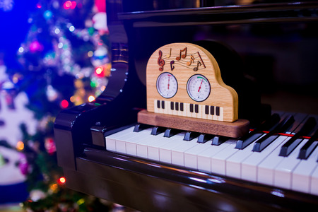 Thermometer and hygrometer there are on piano with Christmas tree for Christmas holiday background. New Year holidays background.