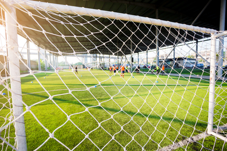 White mesh goal with blurry young boy soccer players sitting with coach on green artificial turf.