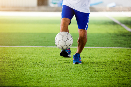 Soccer player speed run to shoot ball to goal on artificial turf. Soccer player training or football match.