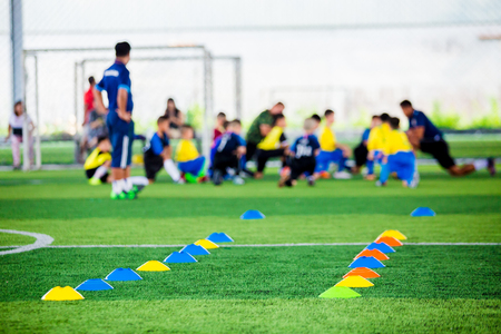 Cone markers is soccer training equipment on green artificial turf with blurry kid players training background. Material for trainning class of football academy